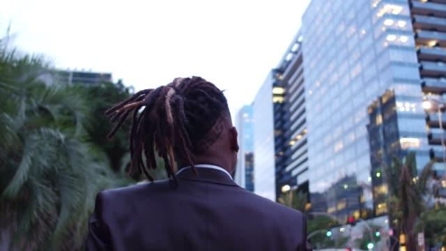 vídeos de stock e filmes b-roll de rear view of a afro businessman walking in the city - viagem de negócios