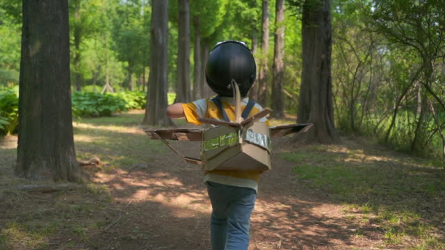rear view of a boy running around in an airplane costume - helmet stock videos & royalty-free footage