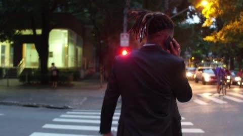 vídeos y material grabado en eventos de stock de vista trasera de un hombre de negocios cruzando la calle, hablando por teléfono - cruzar