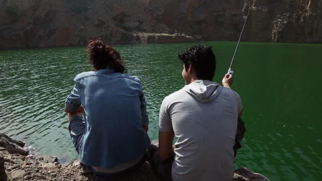 rear view of a couple fishing at riverbank, haryana, india - haryana stock-videos und b-roll-filmmaterial