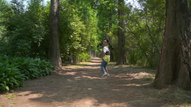 rear view of a girl running around in the woods - rear view stock-videos und b-roll-filmmaterial