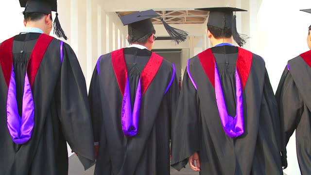 rear view of a group of graduate students walking on a ceremony.(slow motion) - graduation clothing stock videos & royalty-free footage