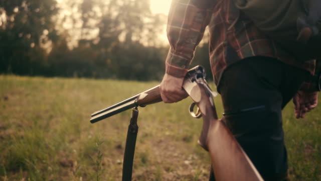 rear view of a hunter walking on the grassland with shotgun (slow motion) - shotgun stock videos & royalty-free footage