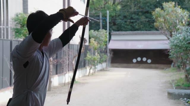 blick zurück auf einen japanischen bogenschützen, der in seinem dojo praktiziert - trefferversuch stock-videos und b-roll-filmmaterial