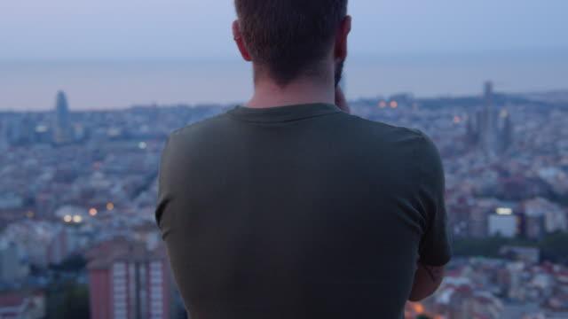 vídeos y material grabado en eventos de stock de rear view of a man from looking at barcelona skyline from a vantage point - un solo hombre