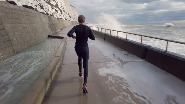rear view of a man running by the sea with waves crashing next to him - rock face stock videos & royalty-free footage