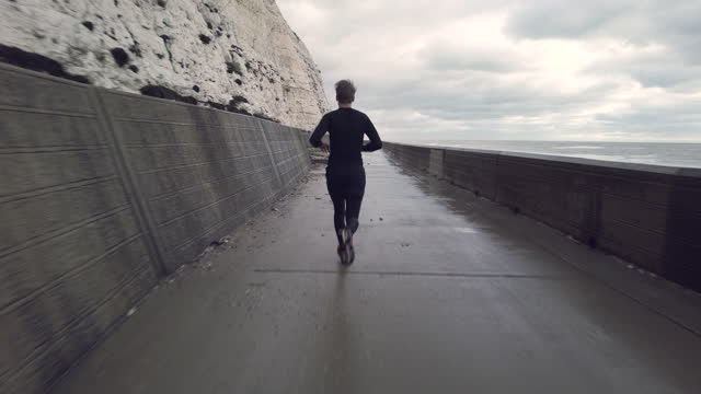 rear view of a man running in the cold grey weather under the cliffs - rock face stock videos & royalty-free footage