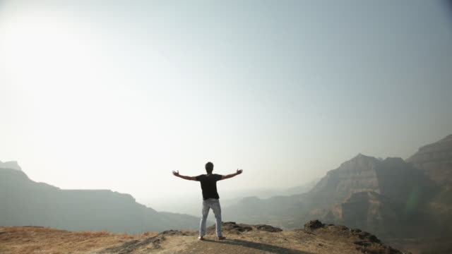 Rear view of a man standing on the cliff of mountain with his arms outstretched