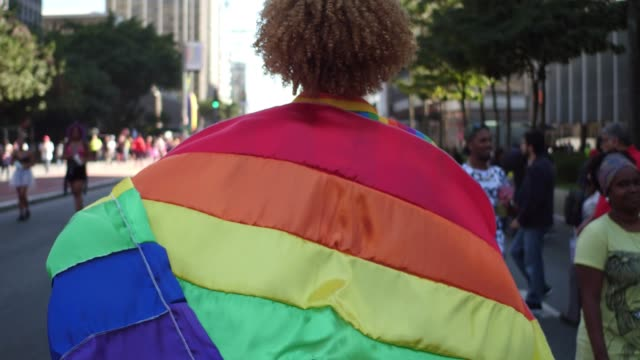 rear view of a man walking with a rainbow flag during lgbt parade - pride stock videos & royalty-free footage