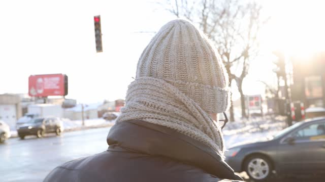 vídeos de stock e filmes b-roll de rear view of a man wearing a tuque waiting at an intersection back lit by winter sunset in a 4k resolution video - back lit