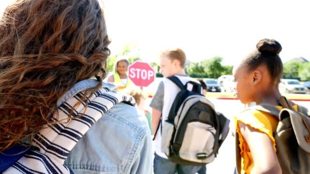 vídeos de stock e filmes b-roll de rear view of a preteen girl waiting to cross crosswalk in front of school - aluna da escola secundária