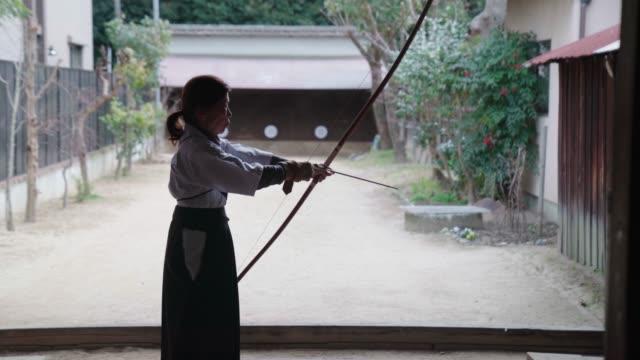 彼女の道場で練習している上級の日本の射手の背面図 - 権力点の映像素材/bロール