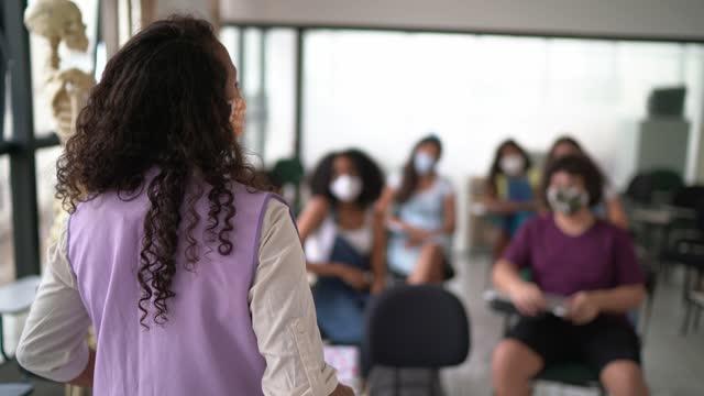 vídeos de stock, filmes e b-roll de visão traseira de um professor na frente da classe ensinando alunos do ensino médio - usando máscara facial - teaching