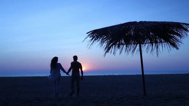 Rear view of a young couple romancing on the beach at sunset