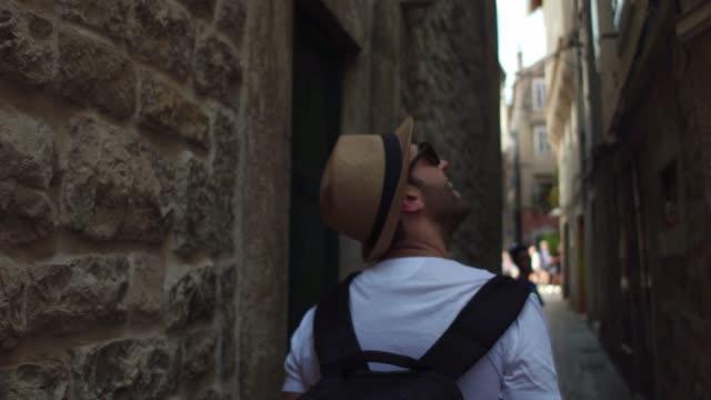 rückansicht eines jungen mannes, der die stadt erkundet - rucksack stock-videos und b-roll-filmmaterial
