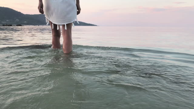 rear view of a young woman enjoying the sea water - walking in water stock videos & royalty-free footage