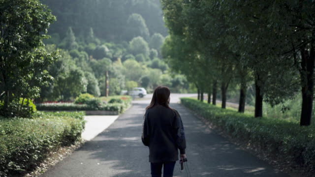 rear view of a young woman walking on the mountain path - zhejiang province stock videos & royalty-free footage