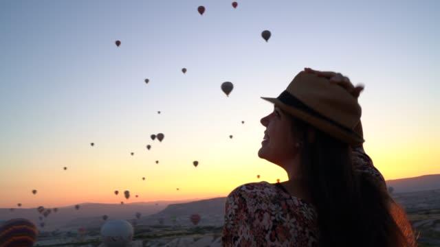 vidéos et rushes de vue arrière d'une jeune femme observant le festival de montgolfière au coucher du soleil - turquie