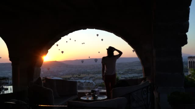 rear view of a young woman watching ballooning festival at sunset - arch architectural feature stock videos and b-roll footage