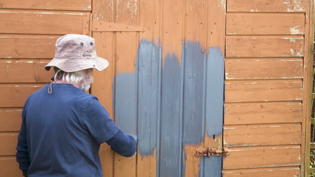 rear view of active senior man painting a shed - one senior man only stock videos & royalty-free footage