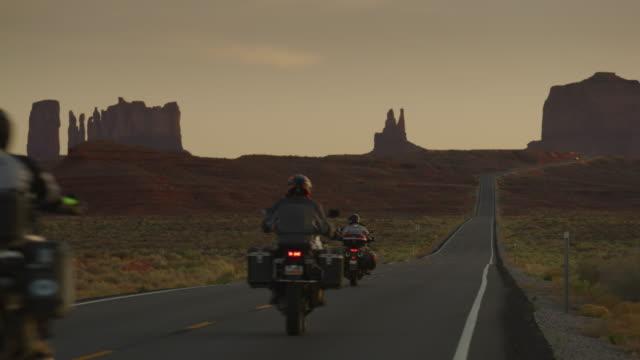 vídeos y material grabado en eventos de stock de rear view of adventure motorcycles riding on freeway at dusk / monument valley, utah, united states - valle monumento