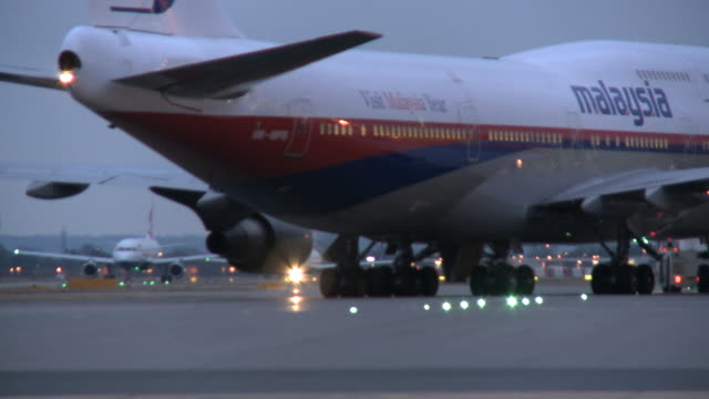 ms rear view of air malaysia boeing 747 being towed on taxiway at dusk, london, united kingdom - taxiway stock-videos und b-roll-filmmaterial