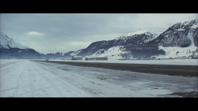 1967 ws rear view of airplane riding down runway in mountain landscape in winter - 1967 stock videos & royalty-free footage