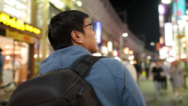 rear view of asian tourist man walking and looking for inspiration of nightlife street in tokyo, japan - food and drink establishment stock videos & royalty-free footage