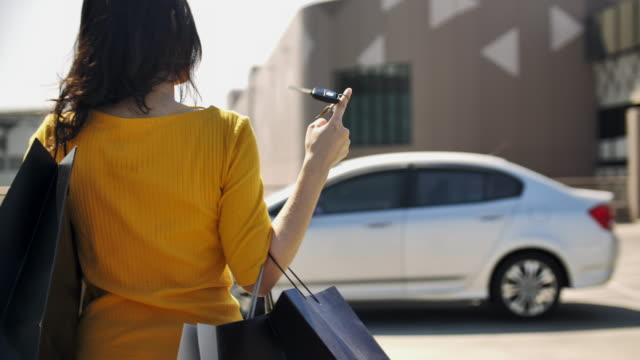 vídeos y material grabado en eventos de stock de vista trasera de la mujer asiática llevando bolsas de compras y llavero caminando de vuelta al coche después del día de compras - pata de animal pierna