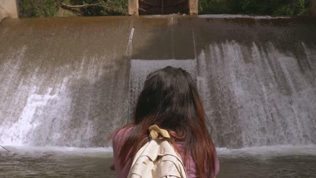 vidéos et rushes de vue arrière de la femme asiatique de tête sur le déversoir local dans la scène de l'agriculture non urbaine, assis pour voir l'eau flottante comme une cascade, le nord de la thaïlande avec se sentir excité, émotion positive - non urban scene