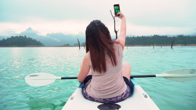 rear view of asian woman using a smartphone to take photos, selfies, taking relaxation among natural blue khao sok lake with outdoor activities, padding with kayak in summer holiday vacation. - natural black hair stock videos & royalty-free footage