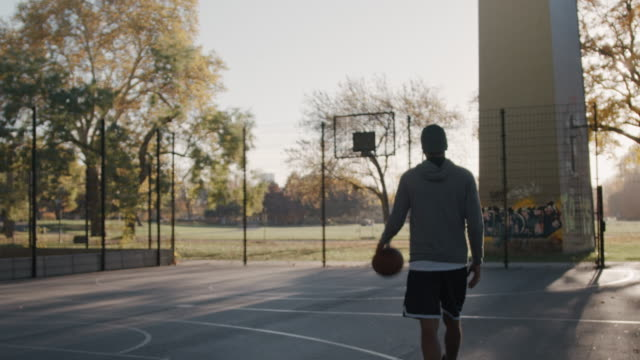 rückansicht des athleten basketballfeld eingeben - basketball stock-videos und b-roll-filmmaterial