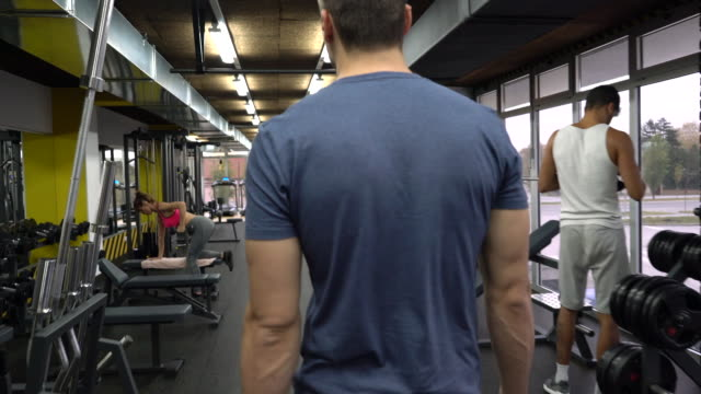 Rear view of athletic man walking through the gym.