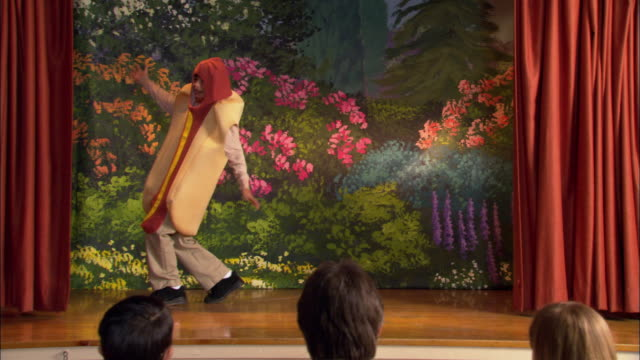Rear view of audience watching curtains part at beginning of school play / boy in hot dog costume dancing on stage / girls in pea pod and carrot costumes entering and shooing boy off stage / girls bowing before audience / parents clapping and taking pictu