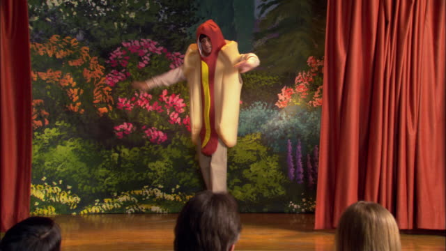 Rear view of audience watching curtains part at beginning of school play / boy in hot dog costume dancing on stage / girls in pea pod and carrot costumes entering and shooing boy off stage / girls taking bow before audience / Los Angeles, California