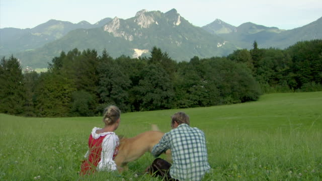 WS Rear view of Bavarian couple in traditional clothing playing with dog on Alpine meadow, Bavaria, Germany