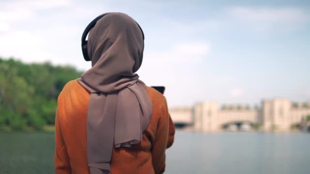 rückansicht der schönen asiatischen mädchen hören podcast im park - religiöse kleidung stock-videos und b-roll-filmmaterial