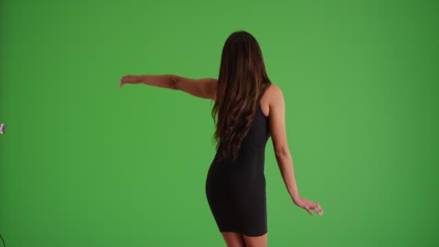 rear view of beautiful cuban woman in tight black dress dancing on green screen - black dress stock videos & royalty-free footage