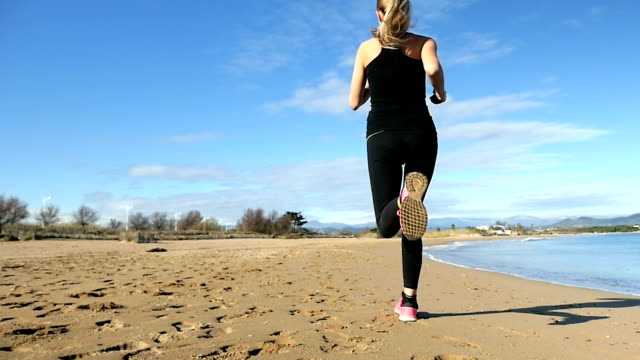 Rear view of beautiful runner on beach