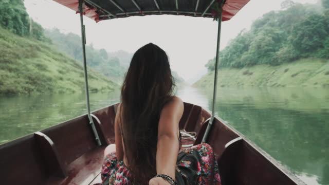 stockvideo's en b-roll-footage met achteraanzicht van mooie vrouw raakt hand met haar man onderweg naar de rivier met groene natuurlijke omgeving - dameskleding