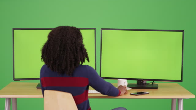rear view of black female on green screen working on computer with greenscreen - weibliche angestellte stock-videos und b-roll-filmmaterial