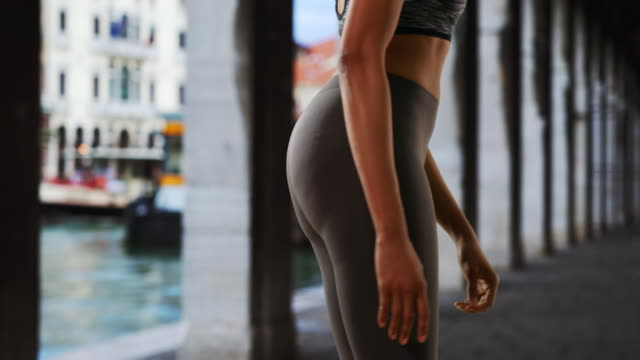 stockvideo's en b-roll-footage met rear view of black woman athlete with fit body stretching her leg - jogster