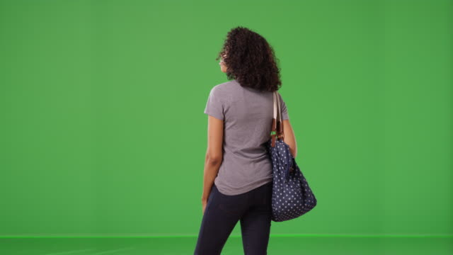 rear view of black woman with big blue polka dot bag standing on green screen - rear view stock videos & royalty-free footage