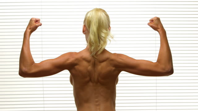 rear view of blonde woman flexing back muscles - flexing muscles stock videos & royalty-free footage