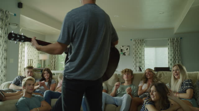 stockvideo's en b-roll-footage met rear view of boy finishing playing guitar for friends in livingroom / cedar hills, utah, united states - tienerjongens