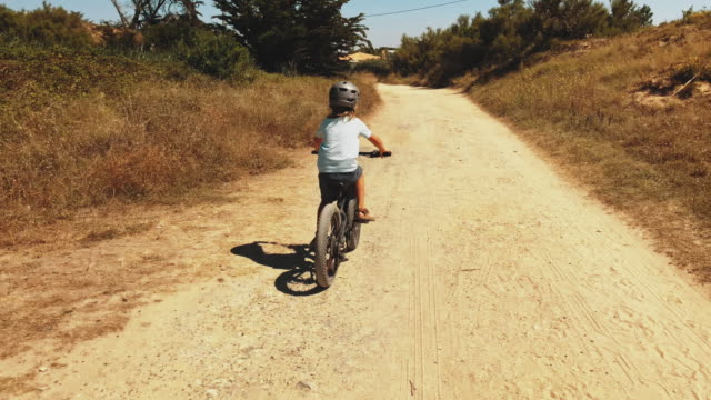 rear view of boy riding bicycle on dirt road - crash helmet stock videos & royalty-free footage