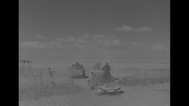 MLS rear view of British armored cars and trucks passing thru opening in barbed wire fence in Libyan desert / MLS British soldier fires antiaircraft...
