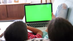Rear View Of Brother And Sister Lying On Sofa At Home Using Laptop Computer