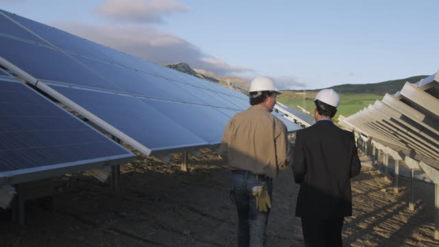 MS DS Rear view of businessman and engineer walking through photovoltaic (solar) plant, discussing project / Malaga, Spain