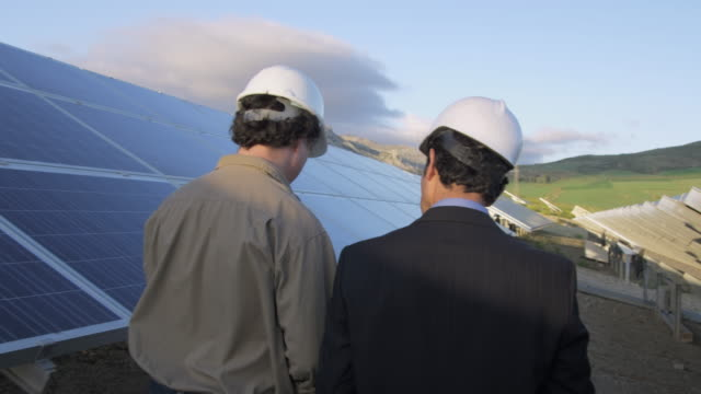 vídeos y material grabado en eventos de stock de cu rear view of businessman and engineer walking through photovoltaic (solar) plant, discussing project / malaga, spain - seguir actividad móvil general